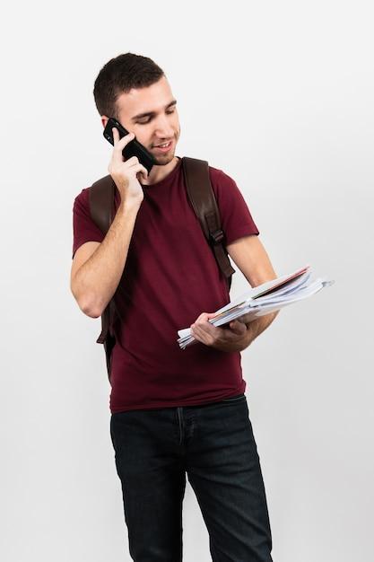 Kerl, der an seinem telefon spricht und anmerkungen hält Kostenlose Fotos
