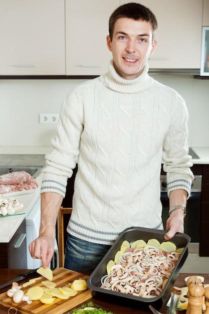 Kerl, der fleisch mit kartoffeln kocht Kostenlose Fotos