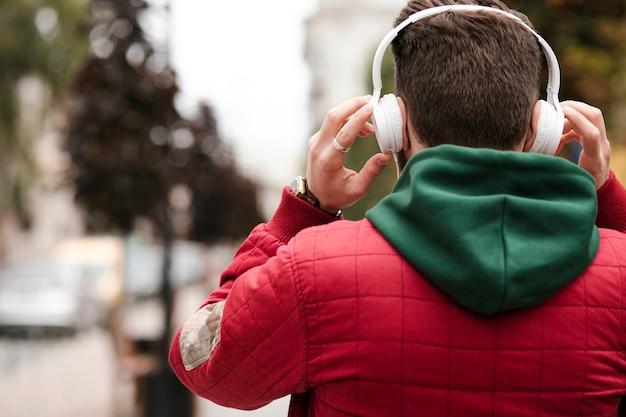 Kerl der hinteren ansicht mit kopfhörern und warmer jacke Kostenlose Fotos