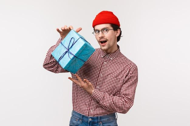 Kerl, der versucht, intrigen als vorbereitetes geschenk für freundin zu machen, verpackte schachtel mit geschenk zu schütteln, sich zu fragen, was drin ist, mysteriöse und gerissene kamera zu sehen, rotes beanie-kariertes hemd zu tragen, Premium Fotos