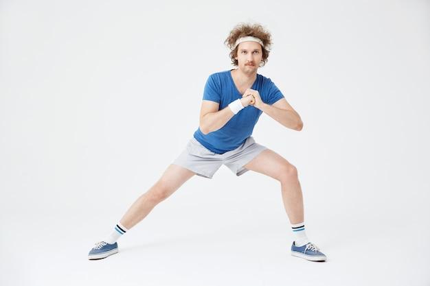 Kerl im retro-sportanzug, der dehnübungen macht. weiß Kostenlose Fotos