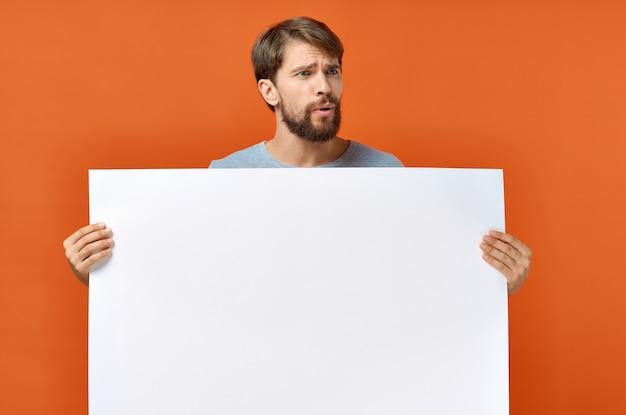 Kerl mit weißem papier auf orangefarbenem plakatmodell-werbeschild Premium Fotos