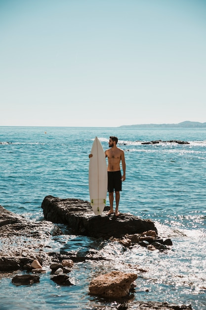 Kerl mit weißem surfbrett auf stein Kostenlose Fotos