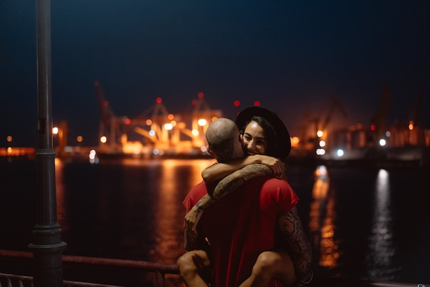 Kerl und mädchen, die auf einem hintergrund des nachthafens sich umarmen Kostenlose Fotos