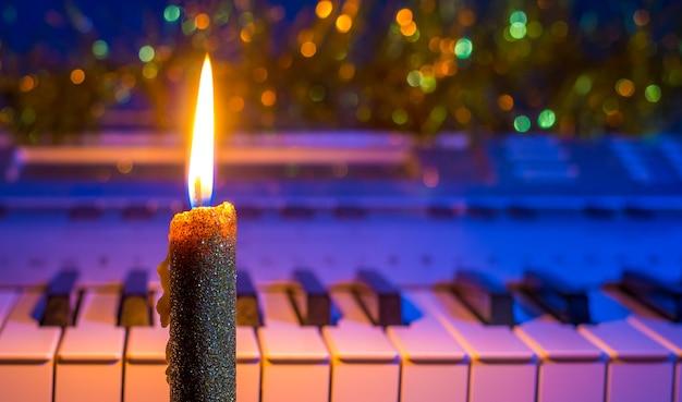 Kerze in der nähe des klaviers weihnachts- und neujahrsmusik Premium Fotos