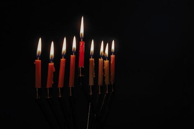 Kerze lite auf dem traditionellen schwarzen hintergrund des silbernen chanukka-menorah Premium Fotos