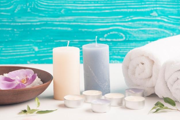 Kerze mit aufgerollter tuch- und badekurortlatte mit orchideenblume auf schreibtisch Kostenlose Fotos