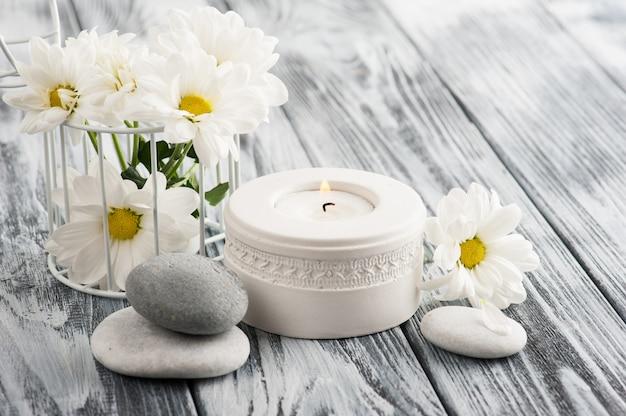 Kerze und steine auf hölzernem hintergrund Premium Fotos