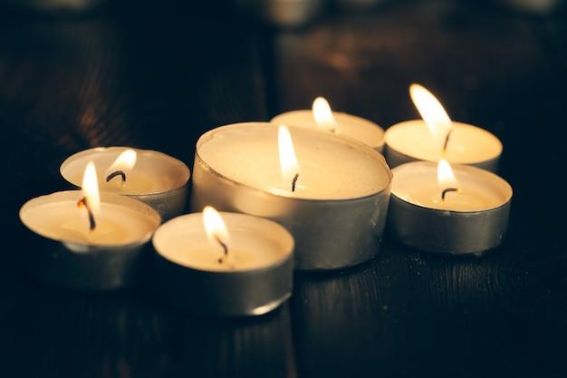 Kerzen brennen in der dunkelheit über schwarz. gedenken. Premium Fotos
