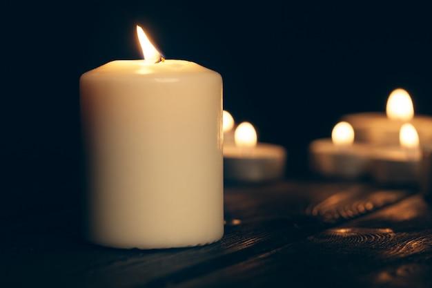 Kerzen brennen in der dunkelheit über schwarz. gedenkkonzept. Premium Fotos