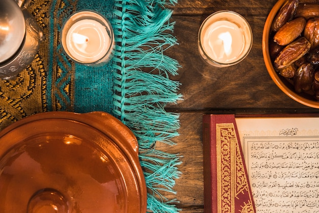 Kerzen in der nähe von koran und datteln Kostenlose Fotos