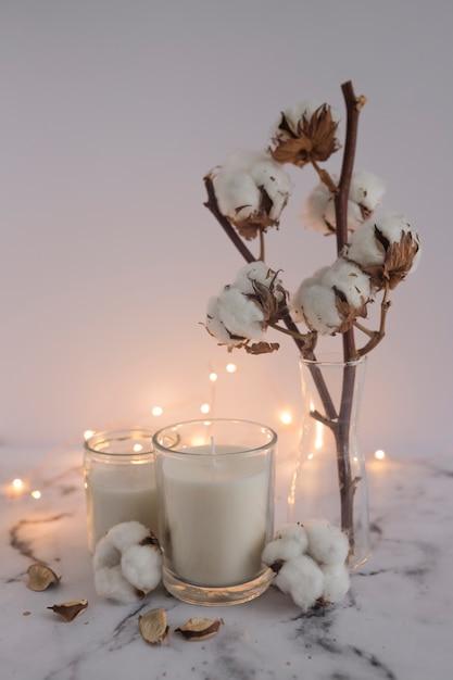 Kerzen mit baumwollzweig und beleuchtungsausstattungen auf marmoroberfläche Kostenlose Fotos