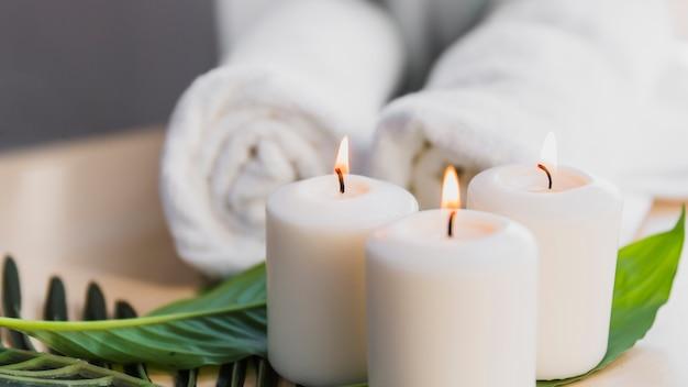 Kerzen und blätter in der nähe von handtüchern Kostenlose Fotos