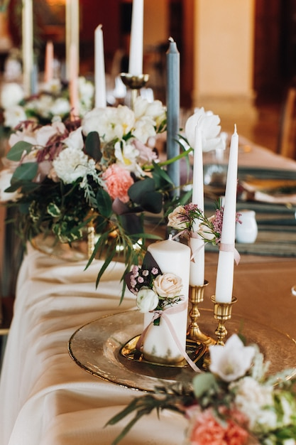 Kerzen und blumensträuße auf dem gedeckten tisch Kostenlose Fotos
