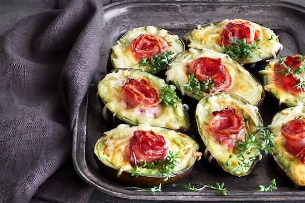 Ketodiätgericht: avocado-boote mit knusprigem speck, geschmolzenem käse und kressesprossen auf dunkelheit Premium Fotos