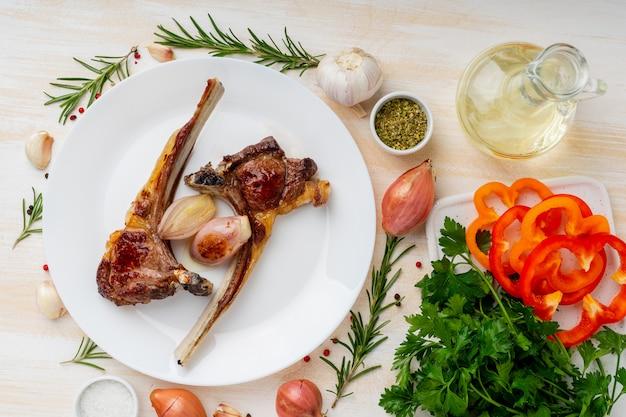 Ketogenic, paleo, lchf diät - fett briet lammrippen auf weißer platte mit gemüse und gewürz Premium Fotos