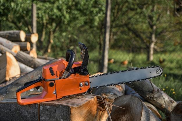 Kettensäge, die auf einem brennholzhaufen im hof auf einem von einer kettensäge geschnittenen brennholz und bäumen steht. Premium Fotos