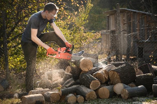 Kettensäge, die auf einem haufen brennholz im hof auf einem schönen grünen gras und wald steht. Premium Fotos
