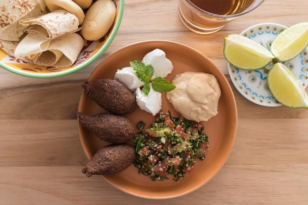 Kibbeh (bulgurweizen / fleischbällchen), labneh, hummus und tabouleh und schüssel mit brot. Premium Fotos