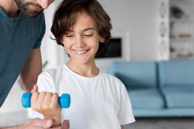 Kid und sein vater treiben zu hause sport Kostenlose Fotos