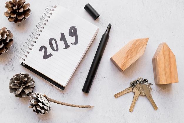 Kiefernzapfen; schlüssel; holzhausblöcke und 2019 auf notizblock mit filzstift auf weiße strukturierte oberfläche geschrieben Kostenlose Fotos