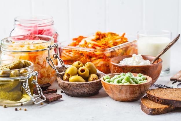 Kimchi, rüben-sauerkraut, sauerkraut, hüttenkäse, erbsen, oliven, brot, schokolade, kefir und eingelegte gurken. Premium Fotos