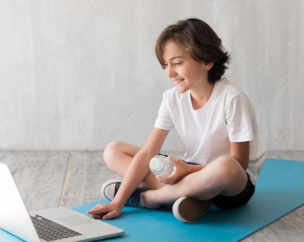 Kind auf dem boden neben dem laptop Kostenlose Fotos