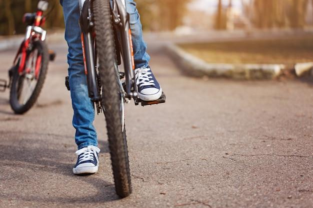 Kind auf einem fahrrad an der asphaltstraße am sonnigen frühlingstag. nahaufnahme auf pedal und fuß Premium Fotos
