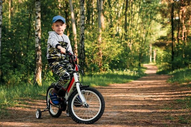 Kind auf einem fahrrad im wald am frühen morgen. junge, der draußen in sturzhelm radfährt Premium Fotos