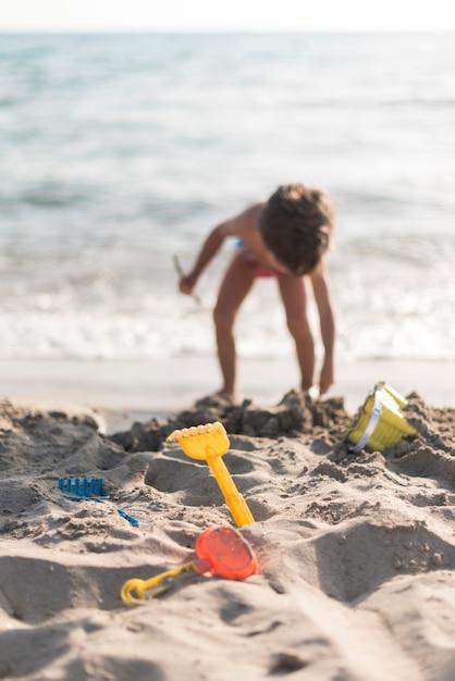 Kind, das am strand mit spielwaren spielt Kostenlose Fotos