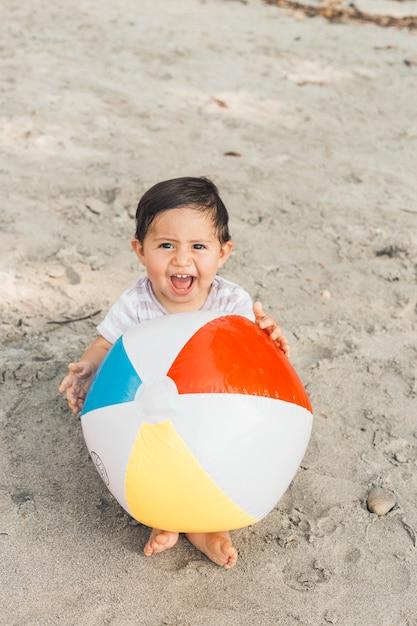 Kind, das auf sand mit aufblasbarer kugel sitzt Kostenlose Fotos