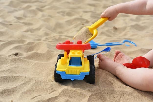 Kind, das auf sand nahe meer spielt. Premium Fotos