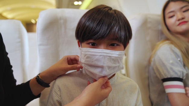 Kind, das gesichtsmaske in einem flugzeug trägt Premium Fotos