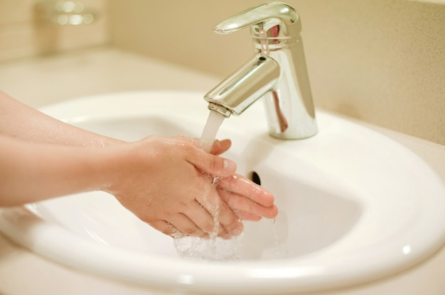 Kind, das hand mit seife wäscht. junge waschen die hand. kinder beim händewaschen im badezimmer Premium Fotos