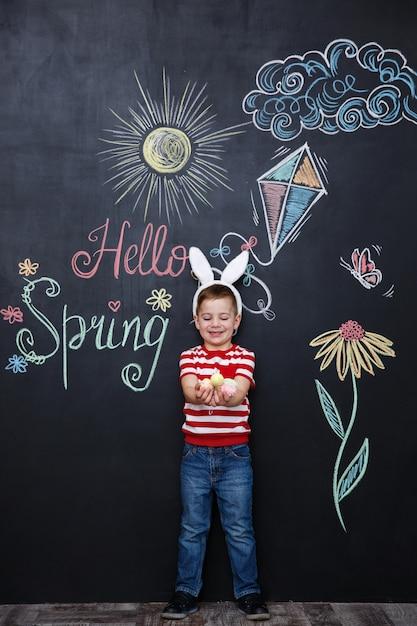 Kind, das hasenohren trägt und haufen von ostereiern hält Kostenlose Fotos