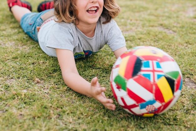 Kind, das im gras liegt und mit ball spielt Kostenlose Fotos