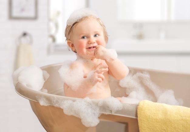 Kind, das in einem badezimmer im schaum sich wäscht. Premium Fotos
