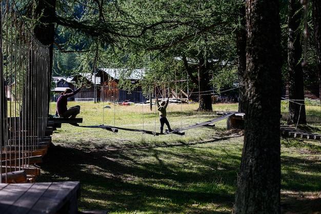 Kind, das in einem familienabenteuerpark in einem europäischen wald spielt. Premium Fotos