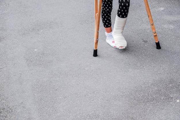 Kind, das krücken und gebrochene beine für das gehen verwendet gebrochenes bein, hölzerne krücken, knöchelverletzung. Premium Fotos