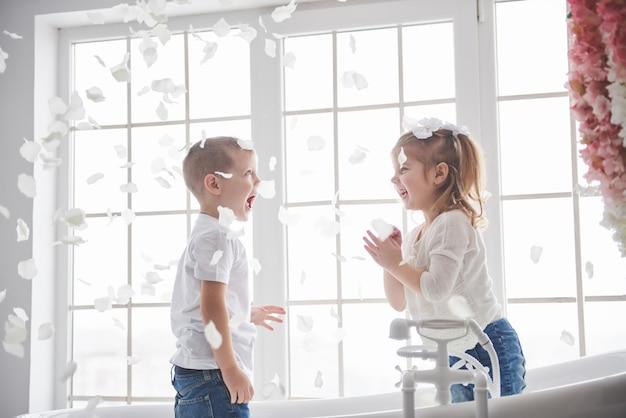Kind, das mit den rogenblumenblättern im hauptbadezimmer spielt. kleines mädchen und junge, die zusammen spaß und freude fawing sind. kindheit und die verwirklichung von träumen, fantasie, phantasie Premium Fotos