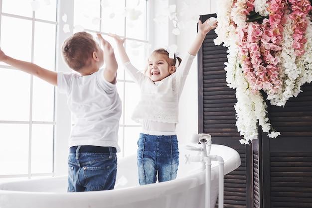 Kind, das mit den rosafarbenen blumenblättern im hauptbadezimmer spielt. kleines mädchen und junge, die zusammen spaß und freude fawing sind. kindheit und die verwirklichung von träumen, fantasie, phantasie Premium Fotos