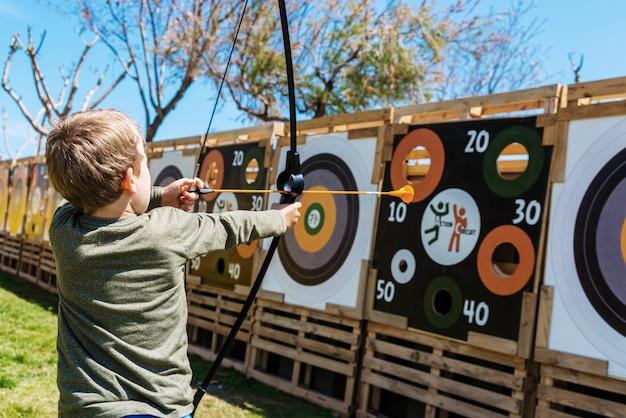 Kind, das mit einem bogen und pfeilen spielt, die sie gegen ein bullauge werfen. Premium Fotos