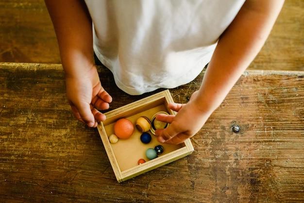 Kind, das mit kleinen spielzeugplaneten auf einem alten holztisch spielt. Premium Fotos