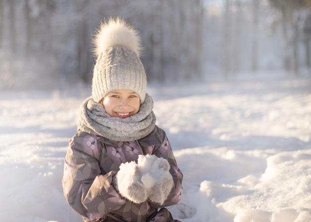 Kind, das mit schnee im winter spielt. kinder fangen schneeflocken Premium Fotos