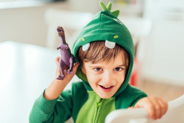 Kind, das mit spielzeugdinosauriern spielt Kostenlose Fotos