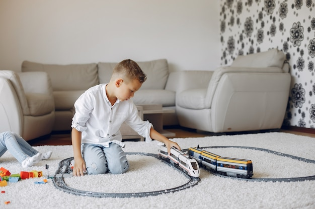 Kind, das mit spielzeugzug in einem spielzimmer spielt Kostenlose Fotos