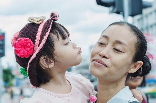 Kind, das mutter, asiatische mutter und kind neckt mit spaß küsst. Premium Fotos