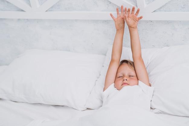 Kind, das nachdem dem aufwachen ausdehnt Kostenlose Fotos
