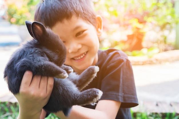 Kind, das reizendes babykaninchen spielt Kostenlose Fotos
