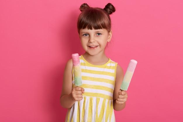 Kind, das zwei eiscreme hält, glückliches kleines mädchen, das wassereis genießt, niedliches kind, das köstliches straßenessen im sommer schmeckt, lokalisiert über rosa wand. Kostenlose Fotos